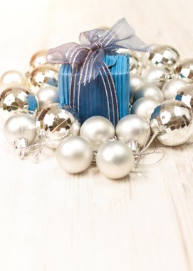 Perspective view of blue giftbox surrounded by silver baubles