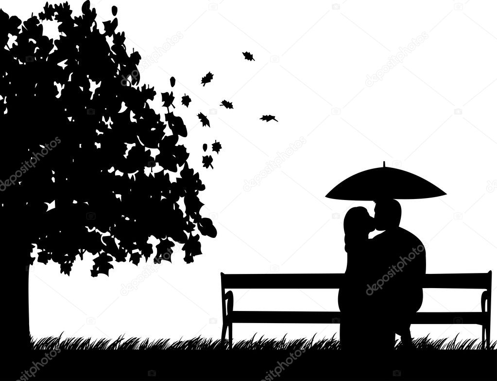 Couple sitting on a park bench and kissing under umbrella in autumn or fall silhouette