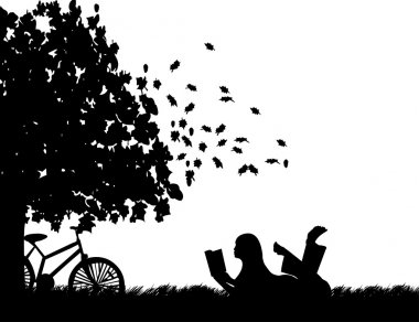 Silhouette of girl with bike reading a book under the tree in autumn or fall