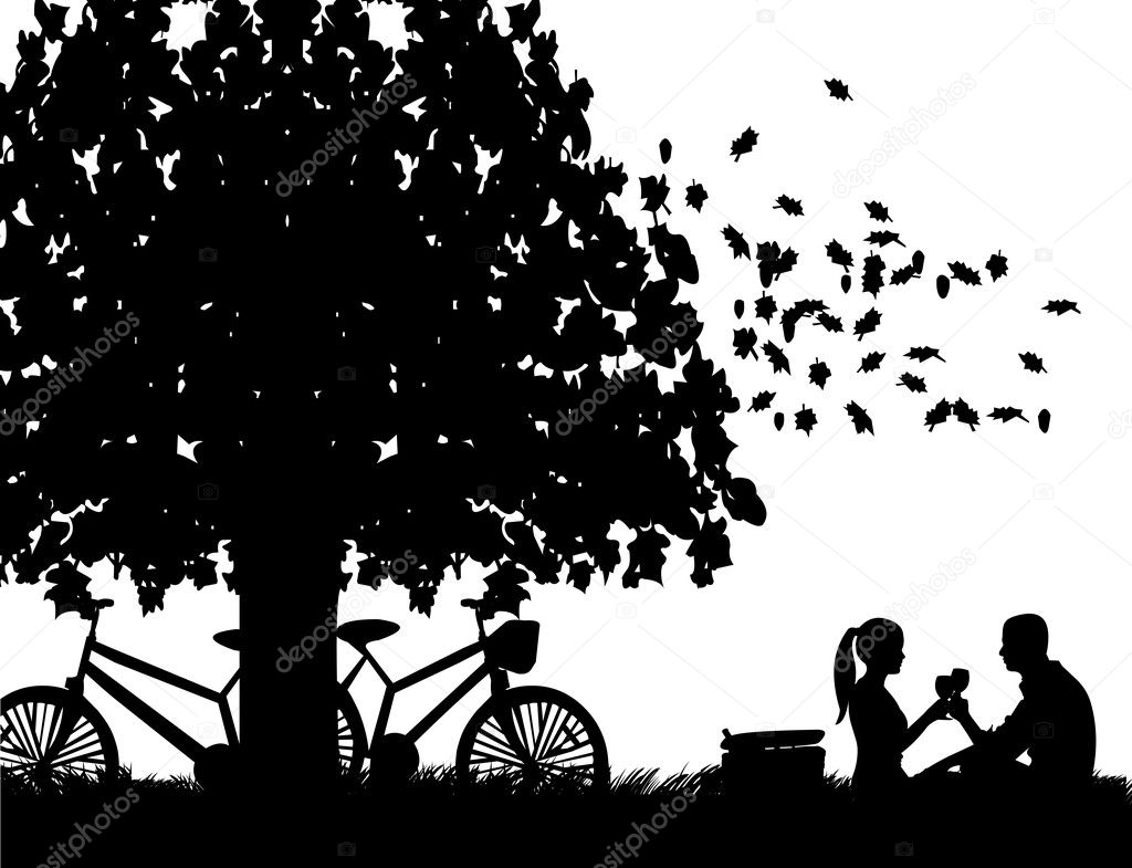 Romantic couple in picnic, with bikes in park under the tree toast with glass of wine in autumn or fall silhouette