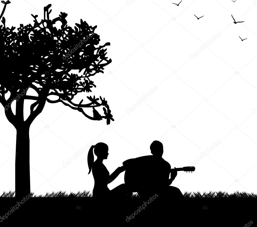 Couple in love where a guy plays guitar in park under the tree silhouette