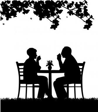 Lovely retired elderly couple drinking coffee in garden under the tree