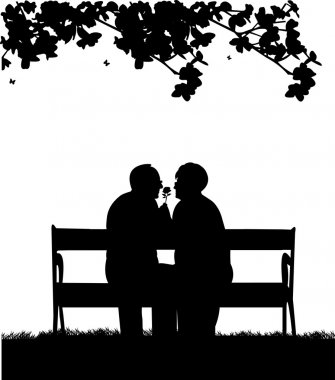 Lovely retired elderly couple sitting on bench in park with flower