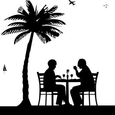 Lovely retired elderly couple having a romantic dinner on the beach under palm tree silhouette