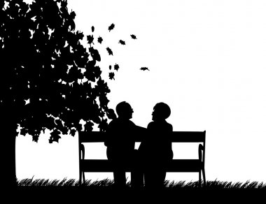 Lovely retired elderly couple sitting on bench in park in autumn or fall