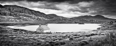 Dramatic landscape with old stone house at a lake on Isle of Mull, Scotland