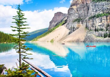 Beautiful landscape with Rocky Mountains and tourists canoeing on azure mountain lake, Alberta, Canada