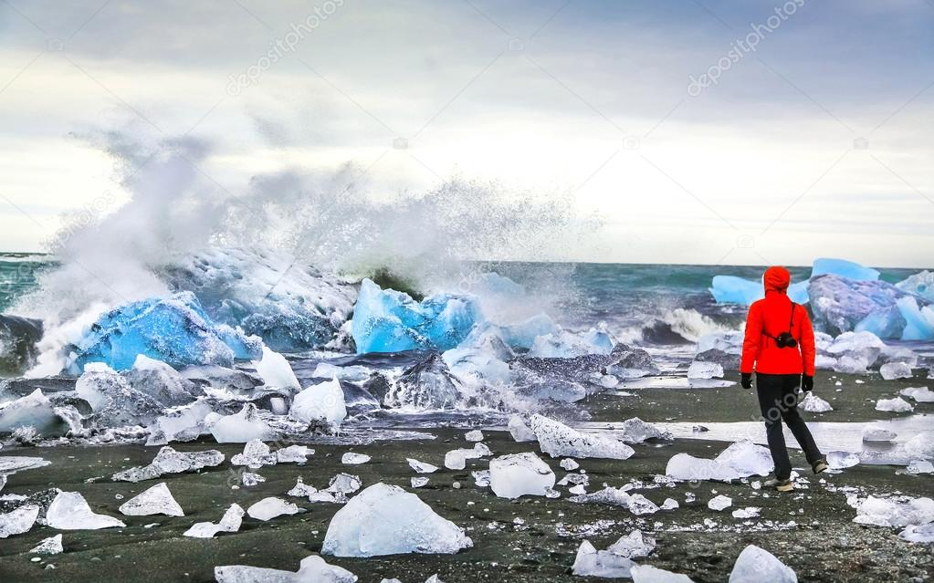 Woman watching waves crash against icebergs at Jokulsarlon glacial lagoon, Iceland