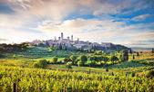 Fotografie wunderschöne Landschaft mit der mittelalterlichen Stadt San Gimignano bei Sonnenuntergang in der Toskana, Italien