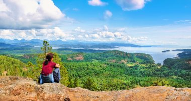 Woman sitting on a rock and enjoying the beautiful view on Vancouver Island, British Columbia, Canada