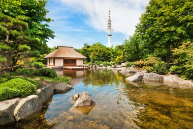 Japanese Garden in Planten um Blomen park with famous Heinrich-Hertz-Turm radio telecommunication tower in the background, Hamburg, Germany