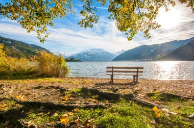 Beautiful autumn scene with park bench and mountain lake in the Alps, Zell am See, Salzburger Land, Austria