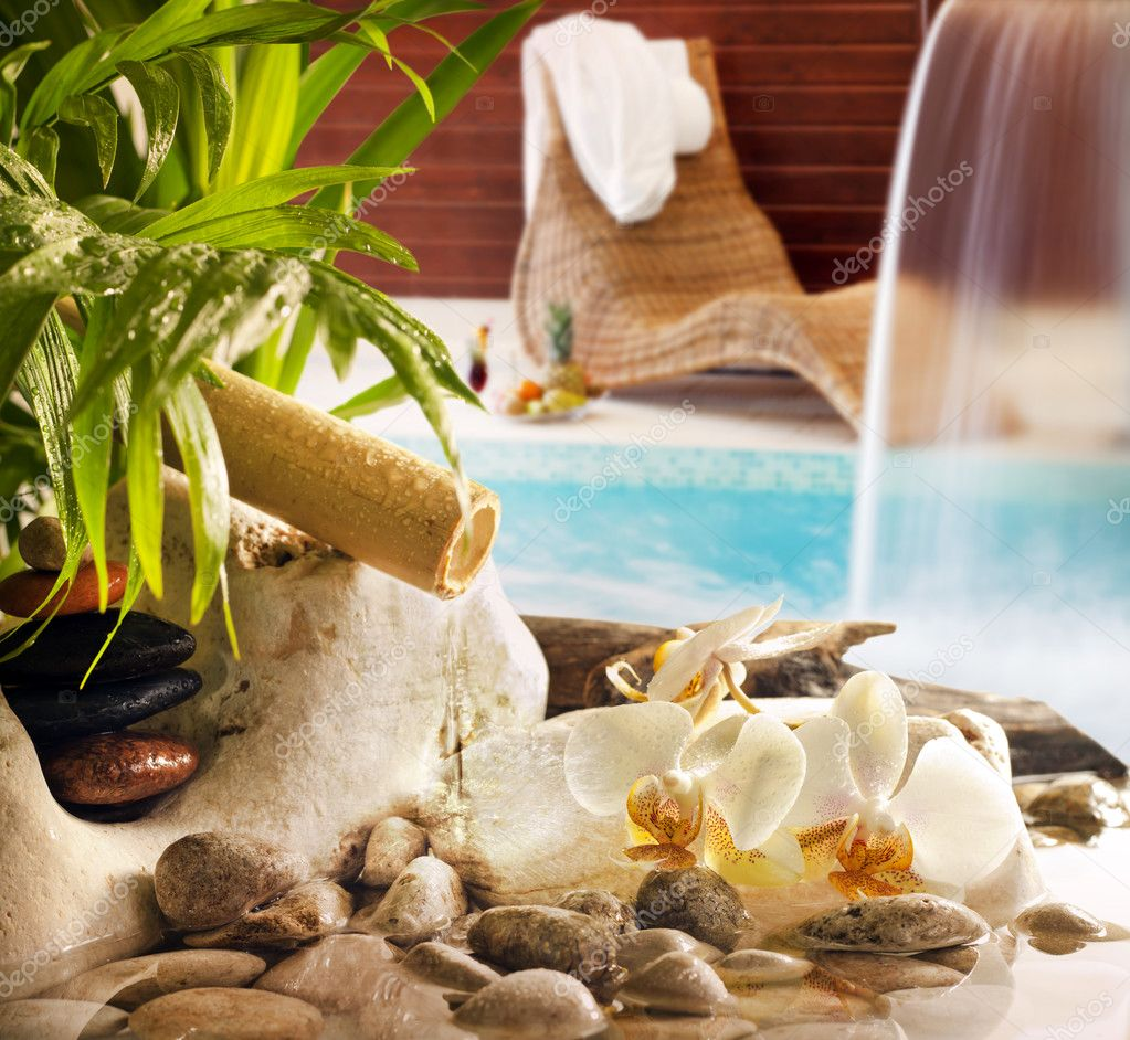 Spa concept with stones orchids waterfall in pool and sunbed