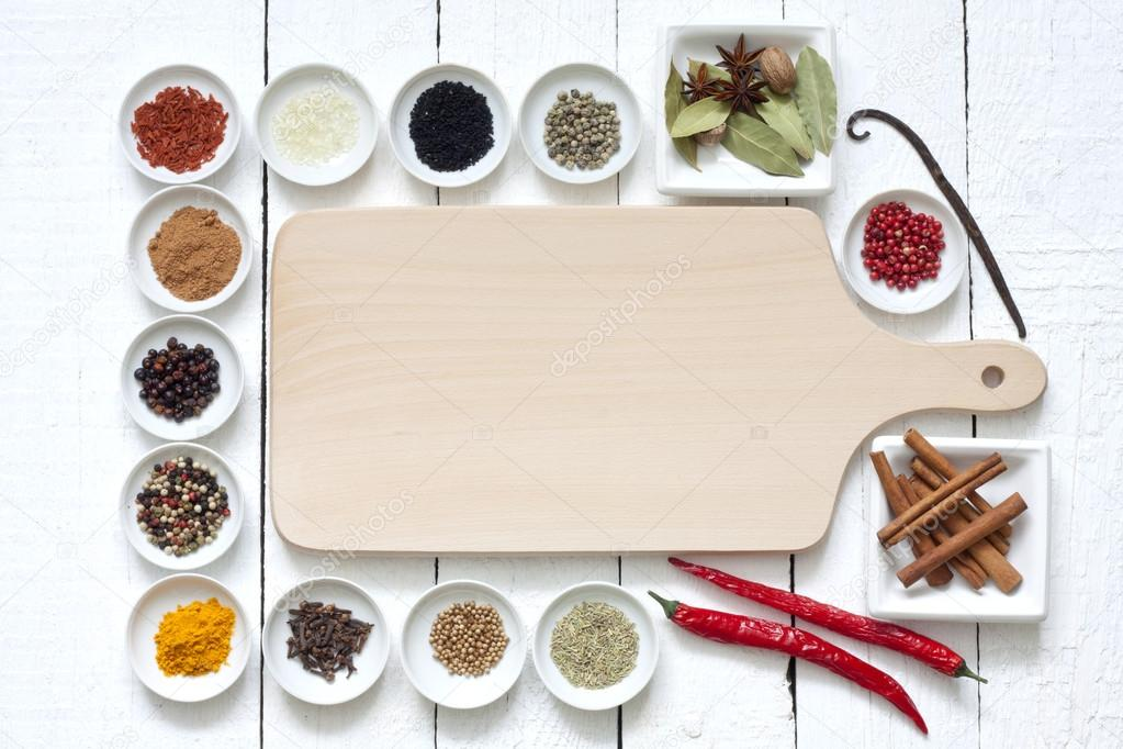 Spices and dried vegetables with cutting board on white planks