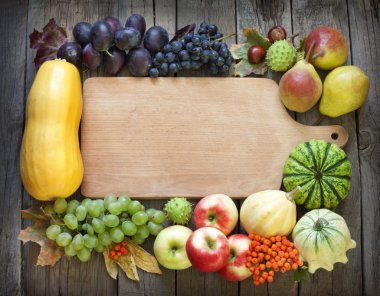 Autumn fruits and vegetables and empty cutting board