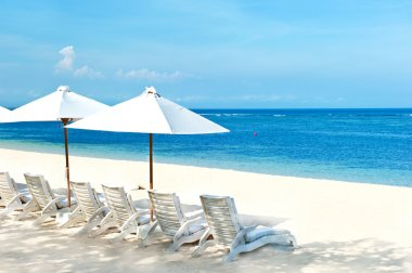 Beach chairs and umbrellas on tropical beach