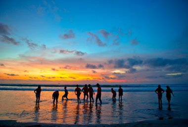 Young at sunset beach in Kuta, Bali