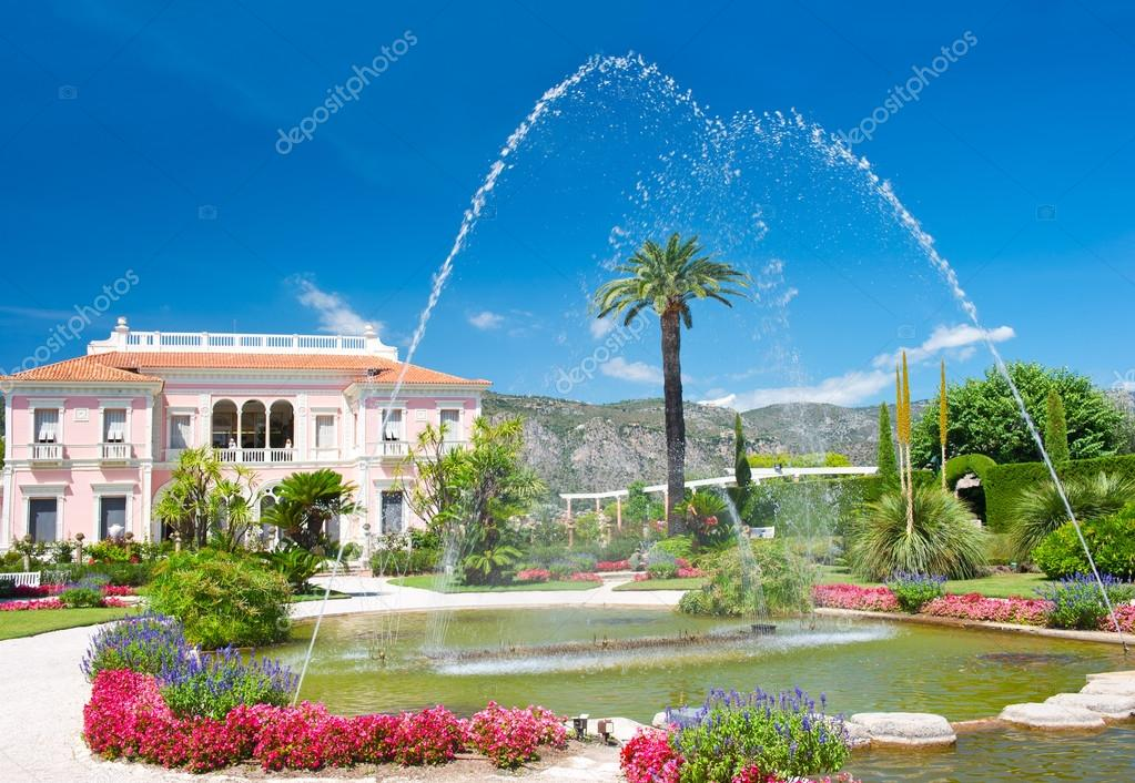 Landscape with fountain, colorful flowers and blue sky