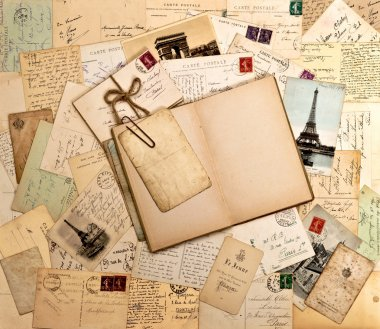 Old letters, french postcards from Paris and open book
