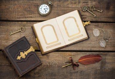 Antique photo album over grungy textured wooden background. vintage keys, clock, glasses, feather pen. nostalgic sentimental picture stock vector