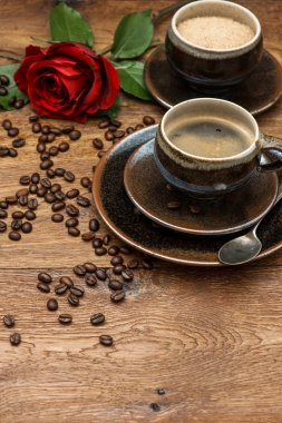 Cup of black coffee and red rose flower