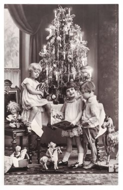Happy kids with christmas tree, gifts and vintage toys