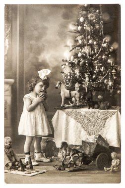 Antique photo of littele girl with christmas tree and vintage to