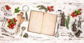 Stará kuchařka se zeleninou, bylinkami a vintage kuchyňské potřeby