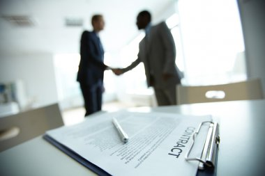 Image of business contract on background of two employees handshaking stock vector