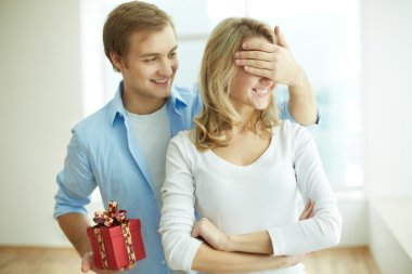 Image of young guy with giftbox closing his girlfriend eyes to make a surprise for her stock vector