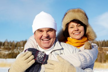 Portrait of happy mature couple in winter clothes looking at camera outside stock vector