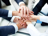 business partners making pile of hands at meeting