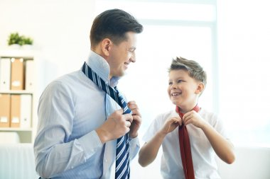 Photo of happy boy and his father tying neckties stock vector