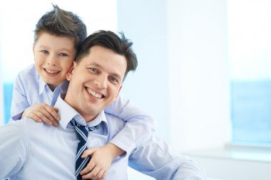 Photo of happy boy embracing his dad and both looking at camera stock vector