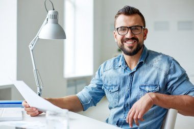 Smiling businessman in denim shirt and eyeglasses looking at camera in office stock vector