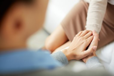 Psychiatrist keeping her hands together with her patient