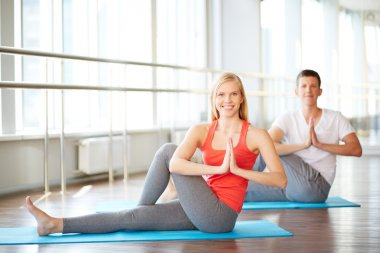Woman doing yoga exercise with guy