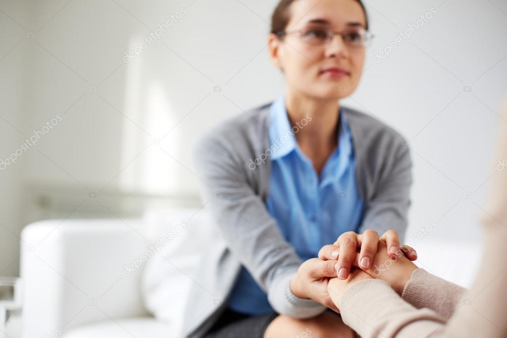 Psychiatrist holding hands of her patient