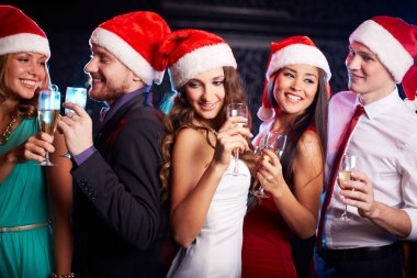 Friends in Santa caps holding flutes of champagne