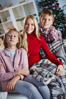 Woman and her two children reading book on Christmas evening
