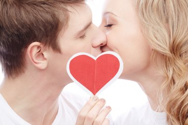 Portrait of young amorous couple kissing while girl holding red paper heart stock vector