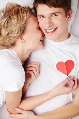 Portrait of happy guy looking at camera with his girlfriend near by holding red heart by his chest stock vector