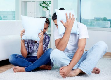 Guy and girl with pillows by faces