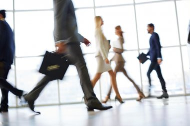 White collar workers going down office corridor