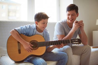 Boy playing guitar with father