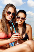 Girls on the beach with beverage