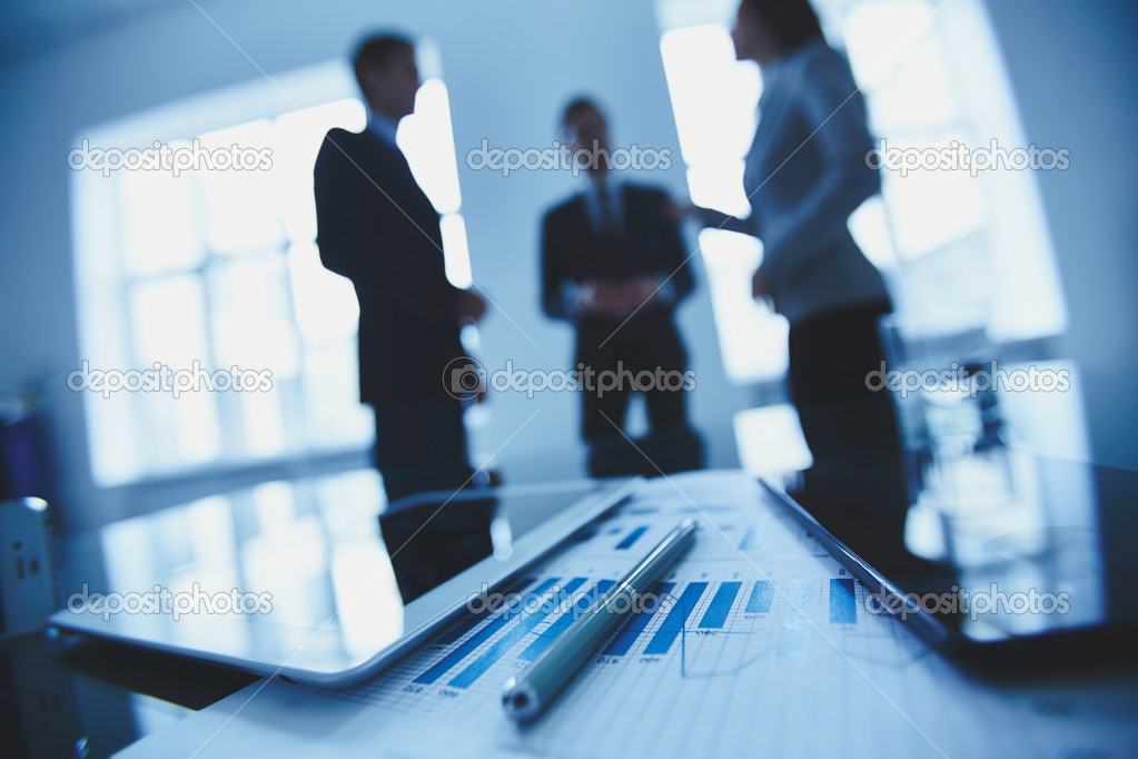 Close-up of business document, pen and touchpads at workplace on background of office workers interacting stock vector