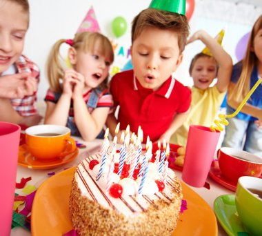 Boy blowing on cake with candles