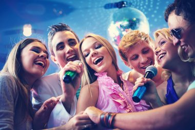 Guys and girls singing at party