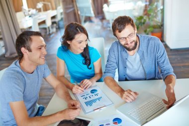 Group of three successful business partners in casual discussing computer project at meeting in office stock vector